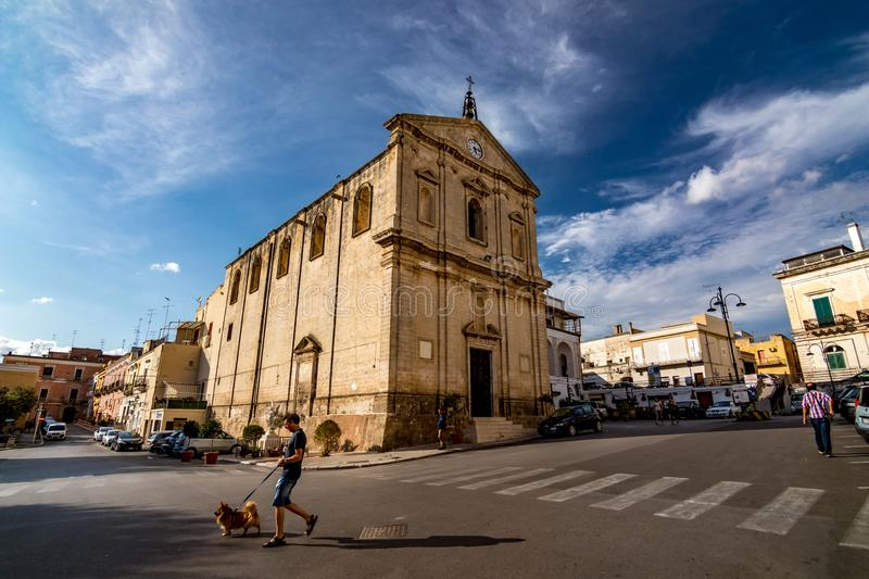 Town life, summer sunny day in Puglia. CASTELLANETA, ITALY - AUGUST 27, 2018 - Public square is almost empty in front of the Church of St. Michele Arcangelo royalty free stock photos