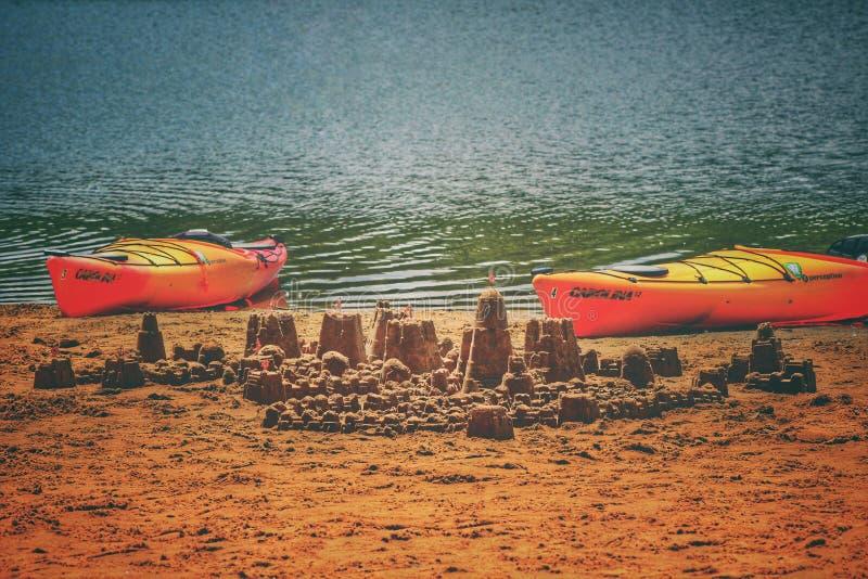 Castelli di sabbia ed una coppia di canoe immagine stock