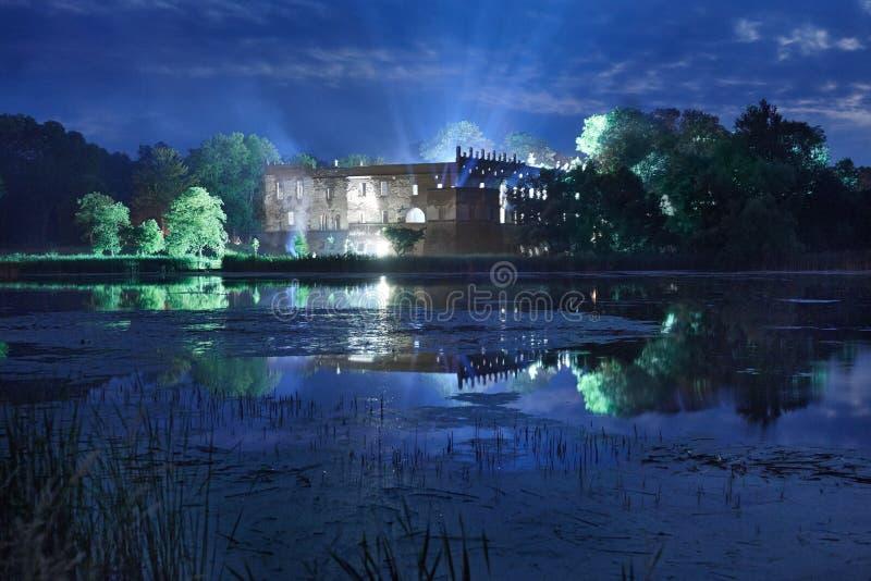 Castello alla notte circondato da un fossato fotografia stock