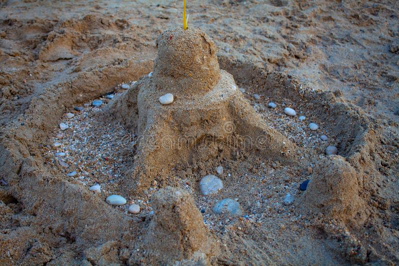 Castello della sabbia sulla spiaggia I bambini giocano con la sabbia Castello fatto della sabbia sulla spiaggia immagini stock