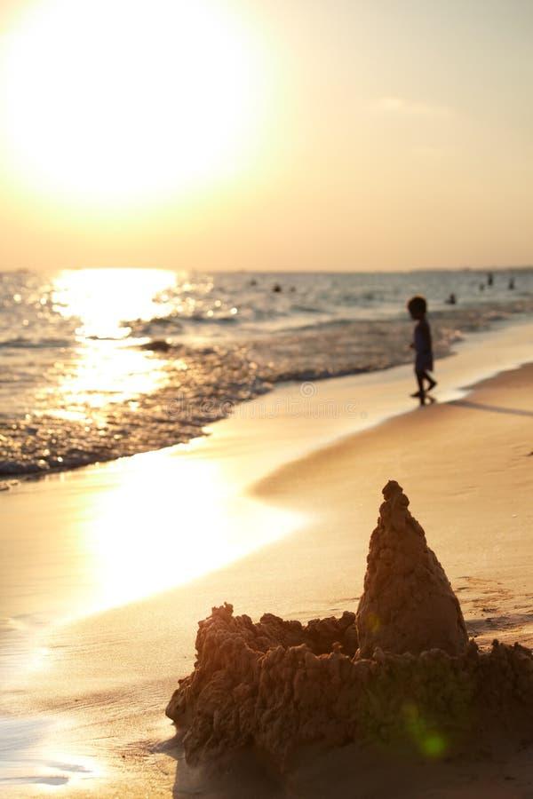 Castello di sabbia sulla spiaggia al tramonto immagine stock