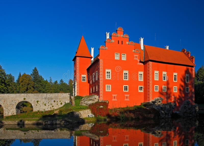 Castello rosso di fiaba sul lago, con il cielo blu scuro, castello Cervena Lhota, repubblica Ceca dello stato fotografia stock