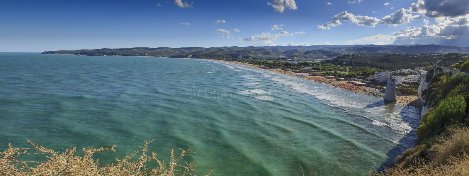 Gargano coast: bay of Vieste,Apulia ITALY. Castello or Scialara beach:it is overshadowed by the Swabiam Castle and the Pizzomunno Monolith from the local royalty free stock photos