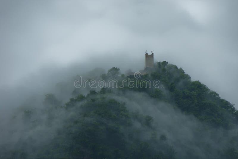 Castello sulla montagna in una nebbia fotografie stock libere da diritti