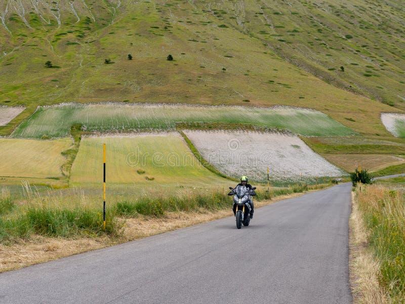 CASTELLUCCIO DI NORCIA, ИТАЛИЯ – 14-ОЕ ИЮЛЯ 2019: Неопознанный мотоциклист на открытой дороге, Castelluccio di Norcia, Италия стоковые изображения
