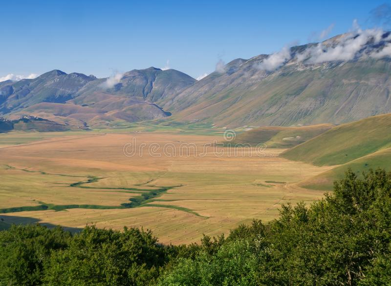 Castelluccio di Norcia, in Umbrien, Italien Felder und Hügel, Apennines hinten, sonniger Tag Bunte Landschaftsansicht herüber stockfoto