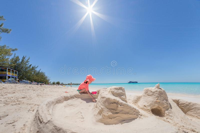 Castelo da areia da construção da moça na praia branca com água azul e o navio de cruzeiros no fundo Alargamento bonito do so fotografia de stock