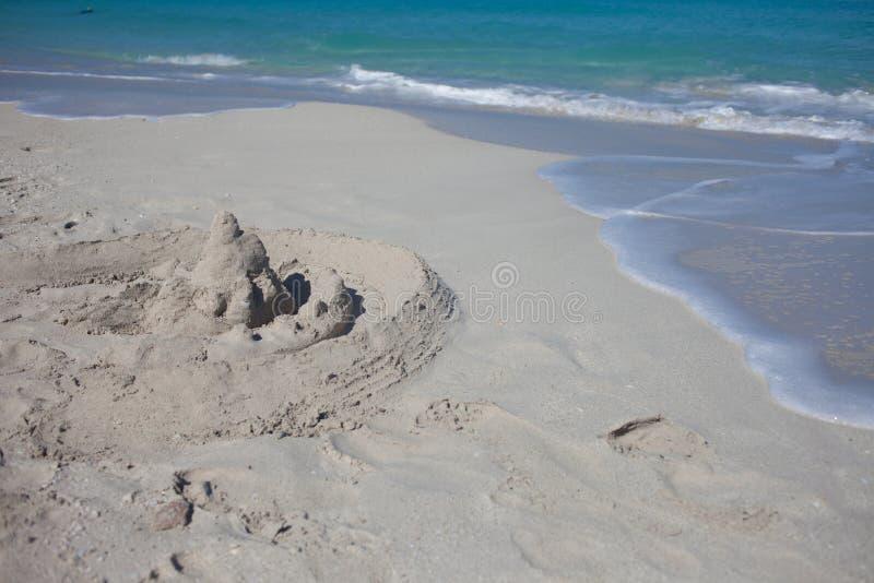 Castelo da areia na praia Casa frágil da areia perto da onda do mar imagens de stock