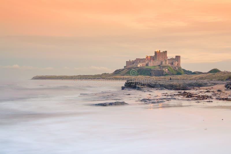 Castelo de Bamburgh em Northumberland no por do sol - vista da praia imagem de stock royalty free