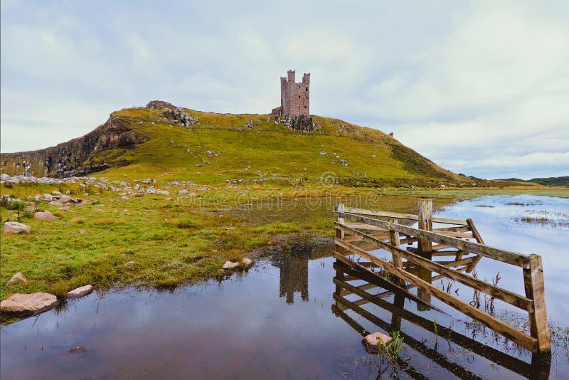 Castelo de Dunstanburgh através da porta fotografia de stock
