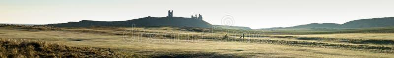 Castelo de Dunstanburgh e opinião os jogadores de golfe foto de stock
