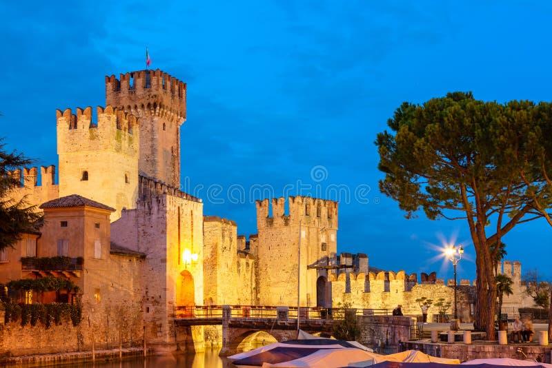 Castelo durante o por do sol da noite, fortaleza medieval de Scaligero na cidade de Sirmione, cercada pelo lago Garda Sirmione, I fotos de stock