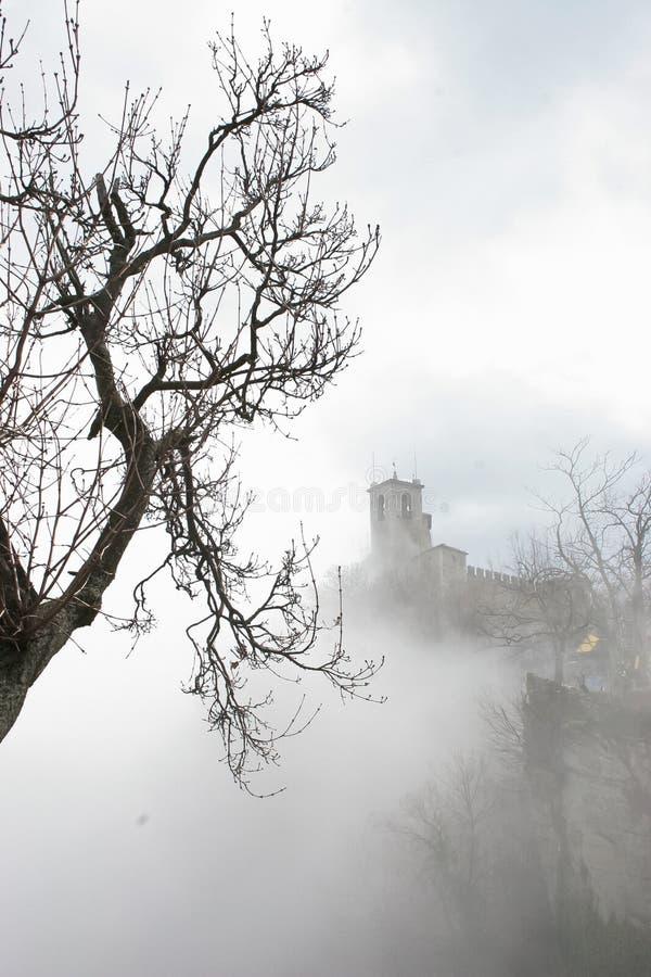 Castelo e árvores antigos na névoa pesada foto de stock