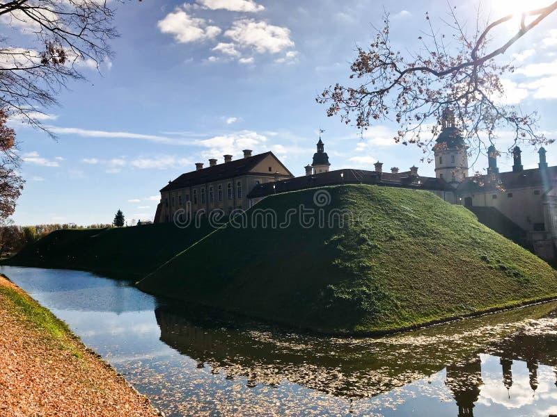 Castelo medieval velho, antigo com spiers e torres, paredes da pedra e tijolo cercado por um fosso protetor com wate foto de stock
