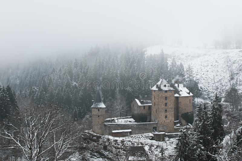 Castelo velho na neve e na névoa foto de stock royalty free