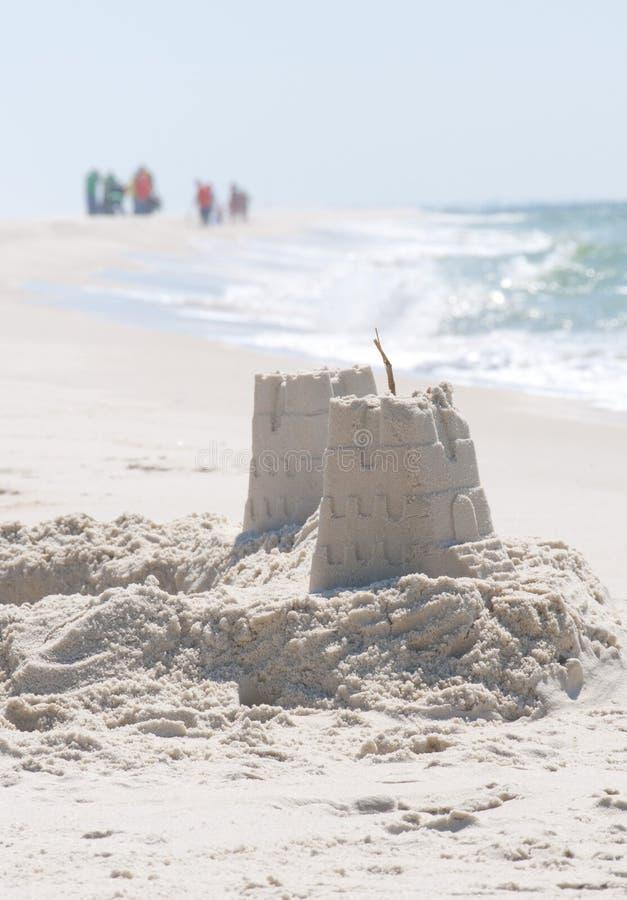 Castelos da areia na praia ameaçada petróleo fotos de stock