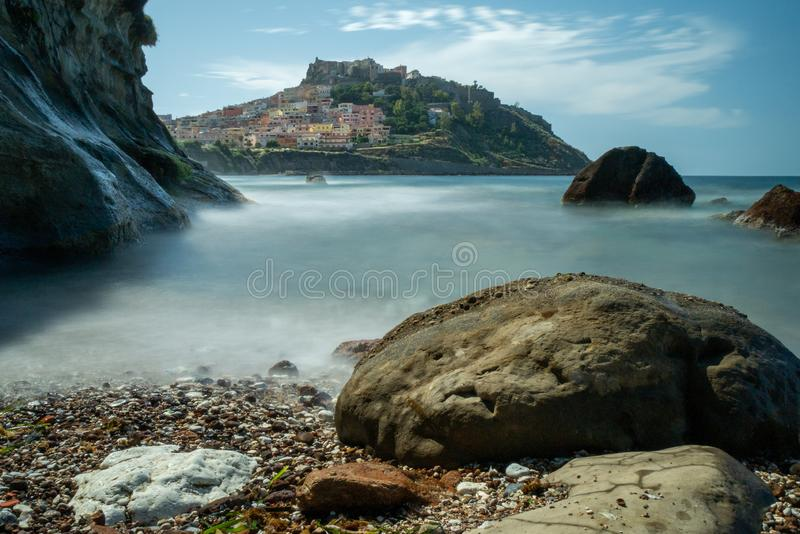 Castelsardo by day. long shuttertime. Castelsardo by day. rock in front. blurry sea long shutter time. dreamy landscape stock image