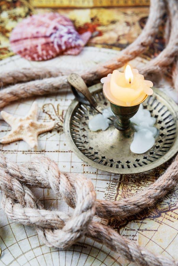 Castiçal com vela e ropare no mapa velho fotografia de stock