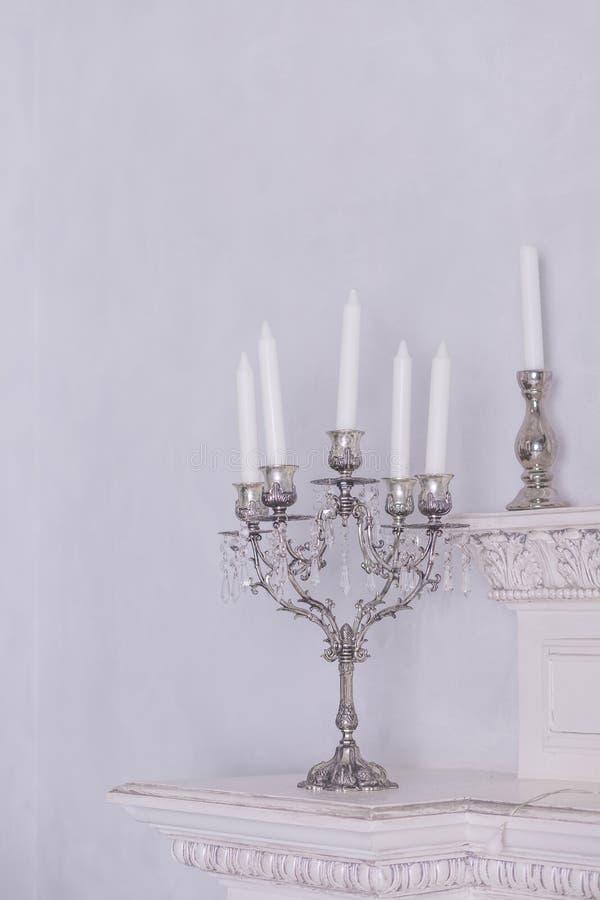 Castiçal de prata retros com as velas brancas, isoladas no fundo branco da parede Imagem vertical Interno claro de Intererniy foto de stock