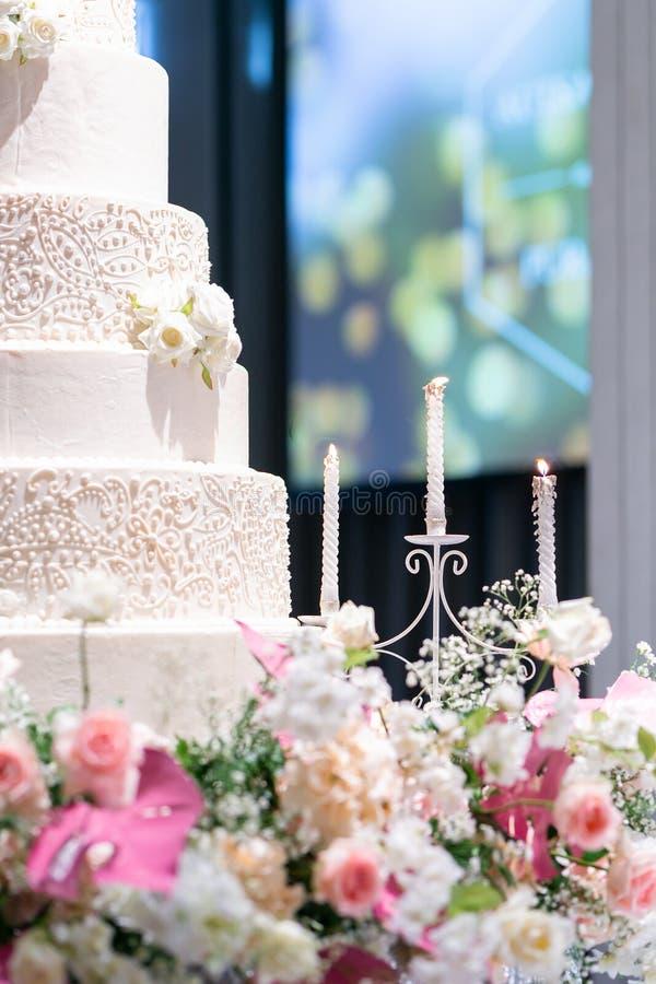 Castiçal e bolo de casamento na tabela de vidro na fase dentro imagem de stock