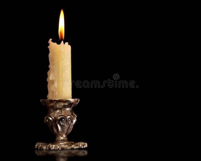 Castiçal velho ardente do bronze da prata do vintage da vela Fundo preto isolado foto de stock royalty free