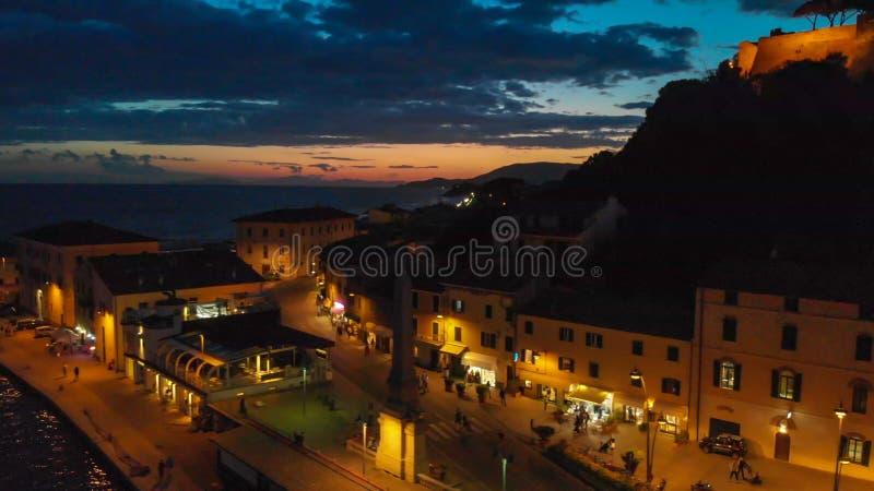 Castiglione della Pescaia på natten, flyg- sikt efter solnedgång fotografering för bildbyråer