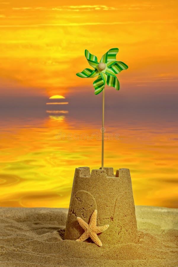 Castillo de arena en la puesta del sol imagenes de archivo