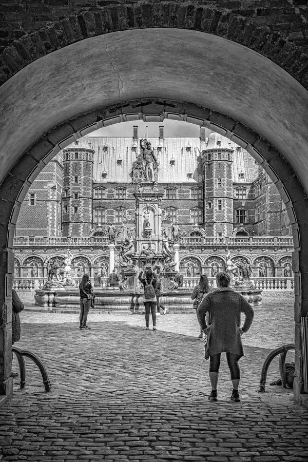 Castillo de Frederiksborg en Dinamarca con los turistas en la arcada foto de archivo