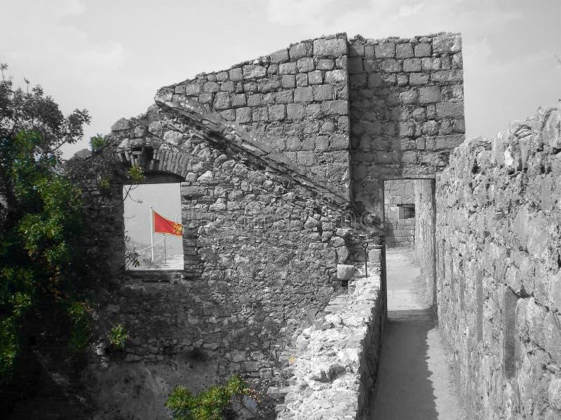 Castillo de Kotor con una bandera roja detrás foto de archivo
