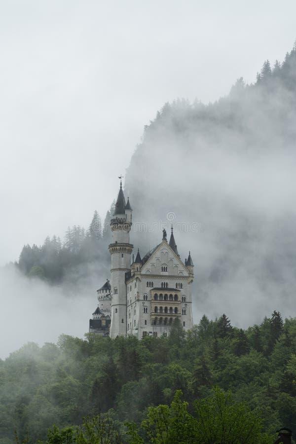 Castillo de Neuschwanstein con misterio y el ambiente de niebla, lugar famoso y destino del viaje en Fussen, Alemania foto de archivo