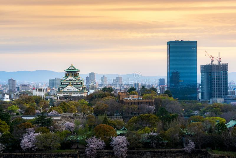 Castillo de Osaka con la flor de cerezo y el distrito financiero del centro en fondo en Osaka, Jap?n fotografía de archivo