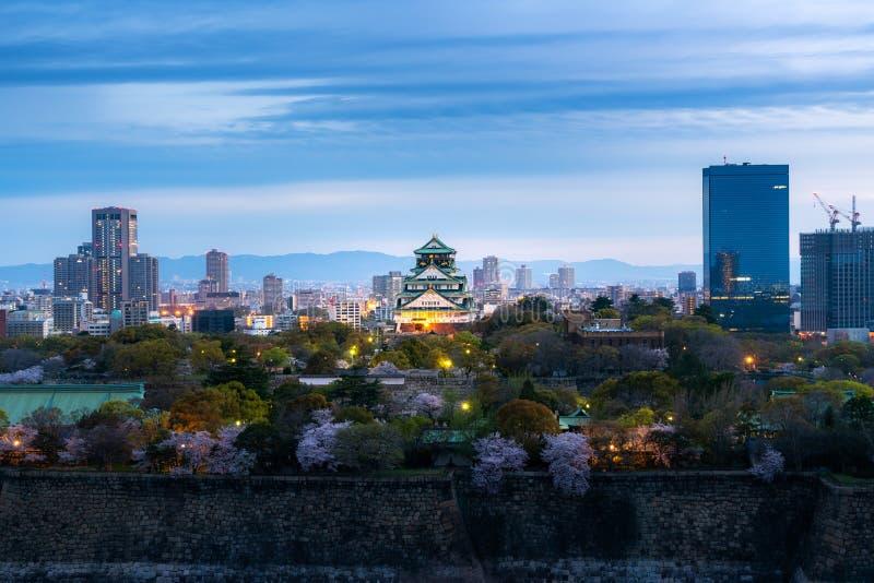 Castillo de Osaka con la flor de cerezo y el distrito financiero en fondo en Osaka, Japón imagen de archivo libre de regalías