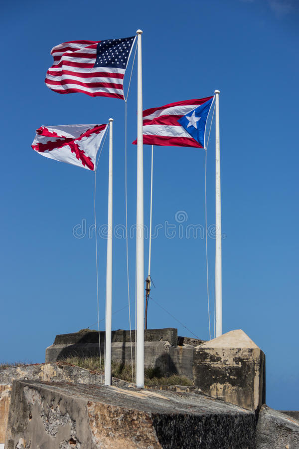 CASTILLO DE SAN FELIPE DEL MORRO, PUERTO RICO, USA - FEB 16, 2015: Three Flags of United States, Puerto Rico and Cross of Burgundy stock photo