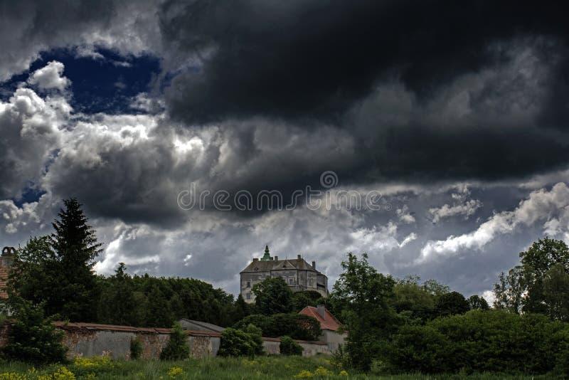 Castillo espeluznante antiguo asustadizo enorme en el top de la colina debajo del cielo nublado oscuro fotos de archivo libres de regalías
