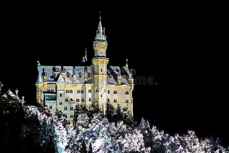 Castillo iluminado de Neuschwanstein en una noche del invierno foto de archivo libre de regalías