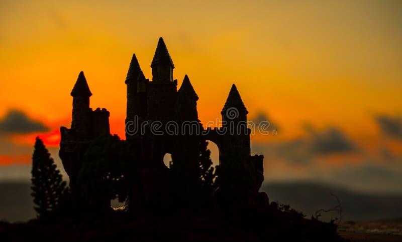 Castillo medieval misterioso en la puesta del sol Castillo viejo abandonado del estilo gótico en la tarde imagenes de archivo