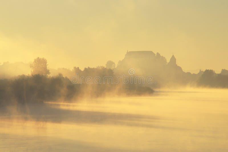 Castillo misterioso en otoño de niebla imagenes de archivo