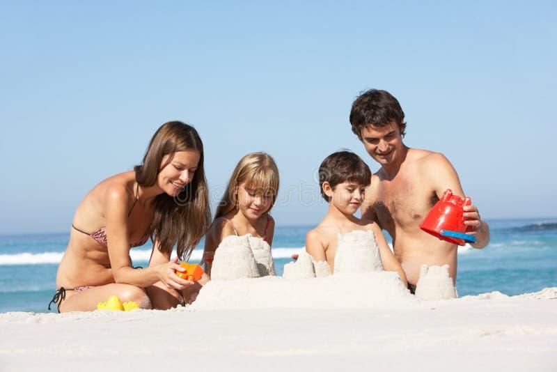 Castillos de arena de la fundación de una familia el día de fiesta de la playa foto de archivo