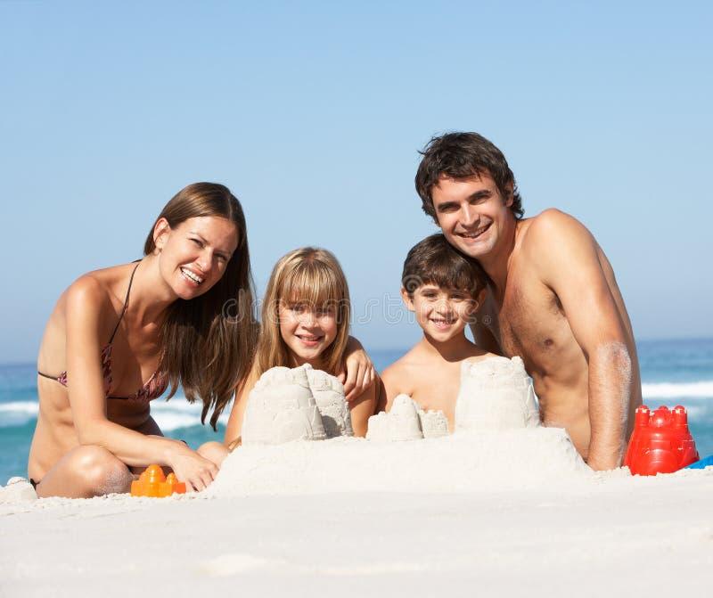 Castillos de arena de la fundación de una familia el día de fiesta de la playa fotos de archivo