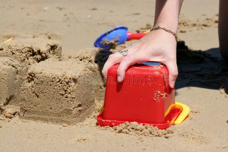 Castillos de arena del edificio en la playa imagenes de archivo