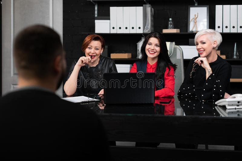 Young man in an interview with three young business women royalty free stock images