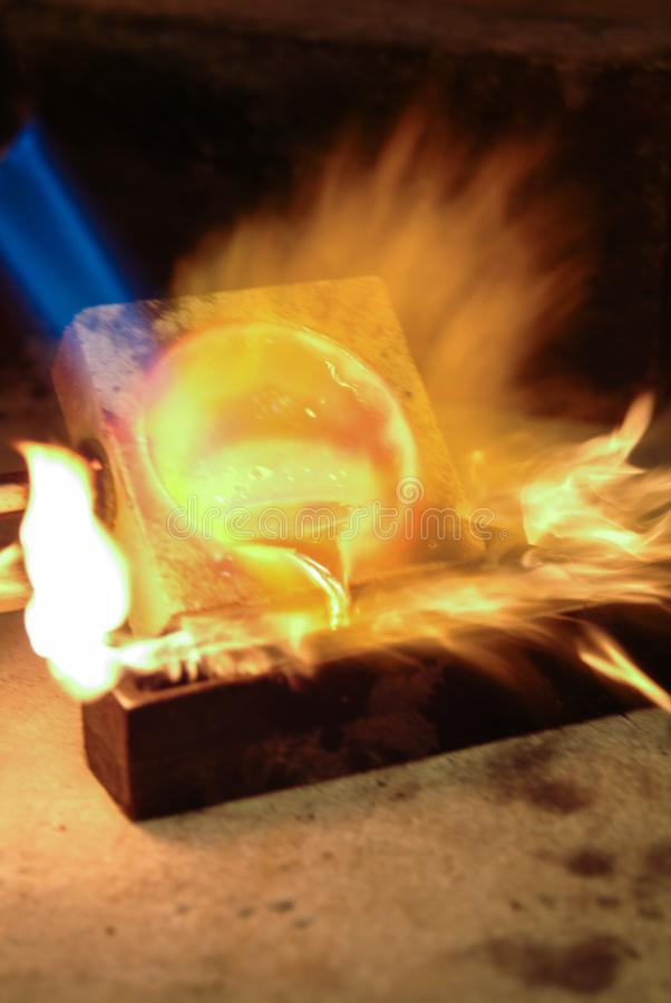 Gold in fusion for ingots with live flames royalty free stock photos