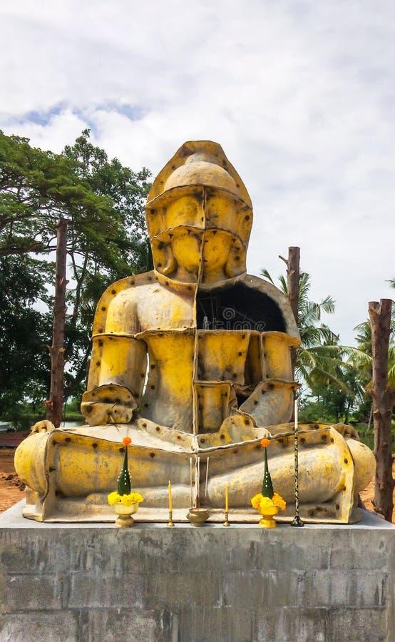 Castingform eine Statue von Buddha in einem gelben Metallbau mit dem Gebrauch des Zementes dort sind Bäume und der Himmel ist der lizenzfreies stockfoto