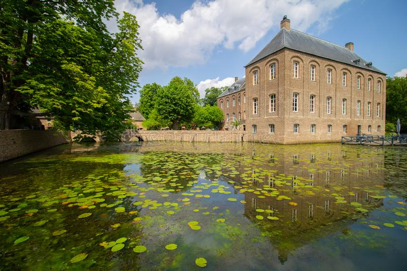 Castle Arcen with reflection on surrounding water. Side view of Castle Arcen  and the surrounding water flowers and green nature. Lelies in the reflective water royalty free stock photography