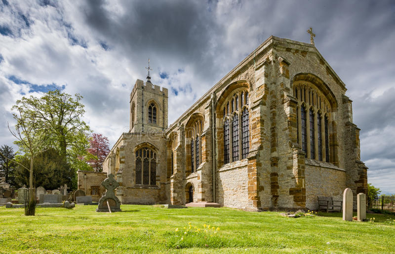 Castle Ashby Church. Low angle image of Castle Ashby church in springtime, showing cowslips, graves, trees and a dramatic sky royalty free stock images