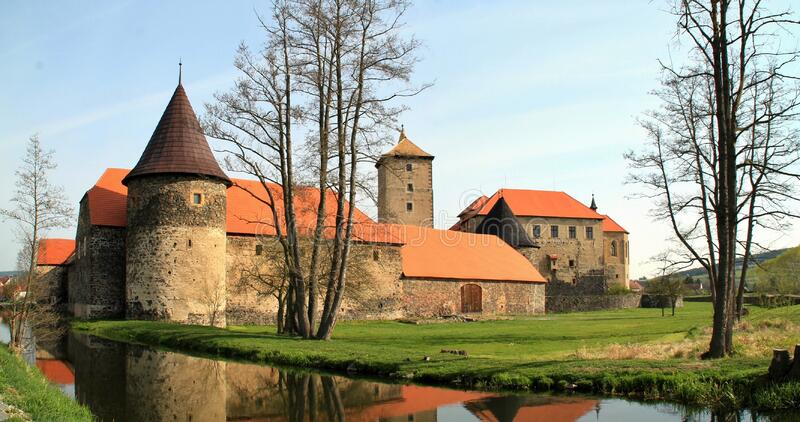 Castle on banks of river stock images