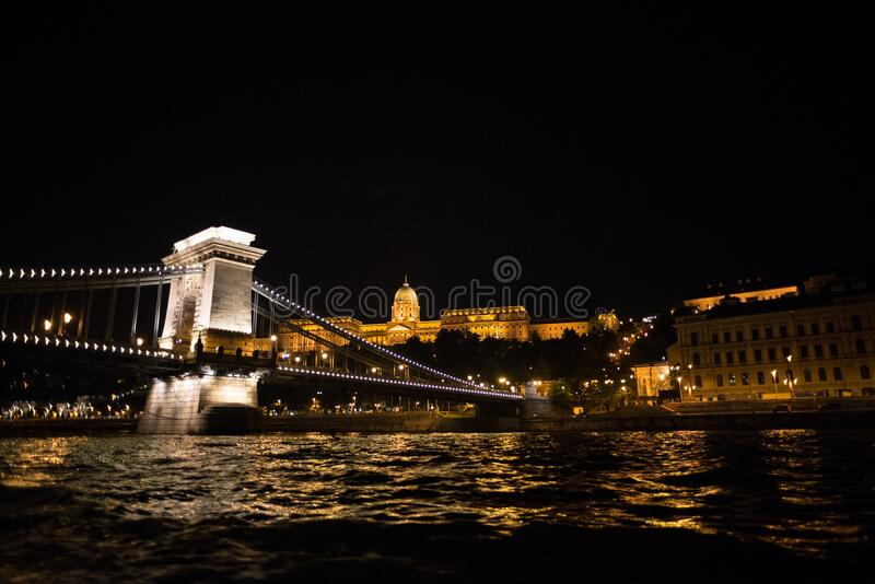 Castle and bridge over Danube River at night royalty free stock photos