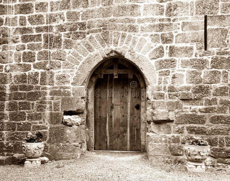 Castle door. Old stone walled castle with a wooden door royalty free stock photo