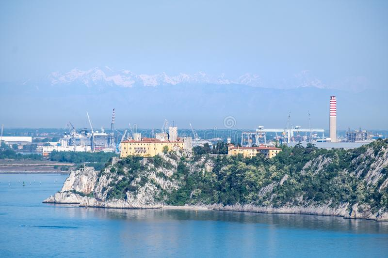 Castle Duino and harbor Monfalcone with mountains alps in Italy royalty free stock photo