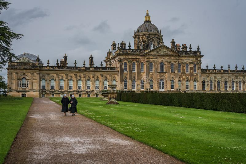 Part of the garden of Castle Howard, with two older nuns in balck. Castle Howard, North Yorkshire, United Kingdom - May 7, 2019 :  Part of the garden of Castle royalty free stock images